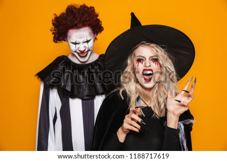 Image of witch woman and joker man wearing black costume and halloween makeup looking at camera isolated over yellow background