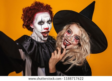 Photo of wizard woman and joker man wearing black costume and halloween makeup taking selfie isolated over yellow background