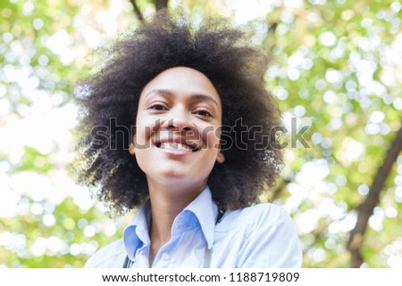 Closeup portrait of lovely young african american woman smiling in nature ,positive face expression, carefree outdoor lifestyle  #1188719809