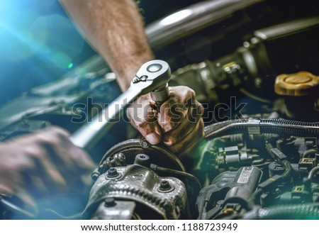 Auto mechanic working on car engine in mechanics garage. Repair service. authentic close-up shot Royalty-Free Stock Photo #1188723949