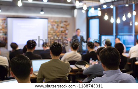 Business People Meeting and Working while Business Executive Lead Presenter Speaks to Group of Successful Technology Entrepreneurs. Consultant Advisor. Growth Training Lecture. Defocused Blurred #1188743011