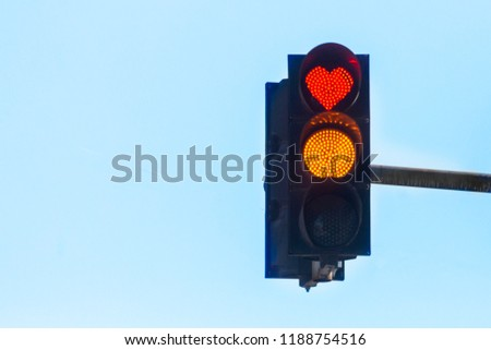 Traffic light with a red heart-shaped signal against a blue sky