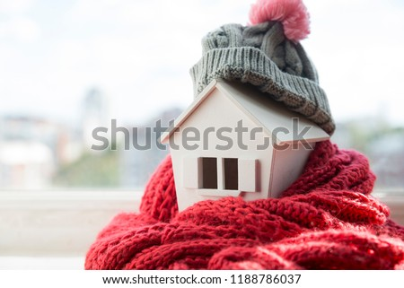 house in winter - heating system concept and cold snowy weather with model of a house wearing a knitted cap #1188786037
