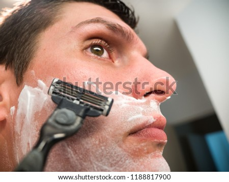 A white Caucasian male looks into the mirror as he prepares to shave his face with shaving cream covering his beard, neck and mustache area. #1188817900