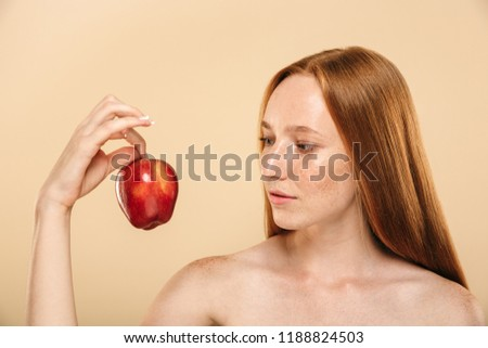 Image of beautiful pretty young redhead woman standing isolated over beige wall background holding apple looking aside. #1188824503