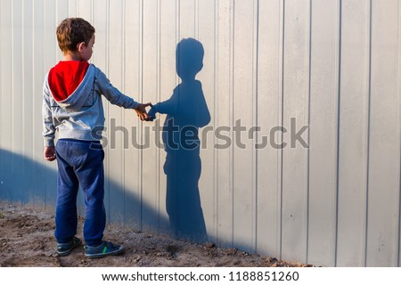 boy and his shadow. Lonely little child playing with his shadow outside. the concept of autism and loneliness. Copy space for your text #1188851260