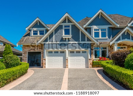 Big custom made luxury house with nicely landscaped and trimmed front yard and driveway to garage in the suburbs of Vancouver, Canada. #1188918097