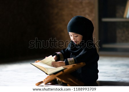 Asian Indonesian Muslim kid is reading the Quran. The Quran is indicated as the guided book for all Muslim and it is direction  to be on the heaven of God.Mosque,Islam,religion and knowledge concept. #1188993709