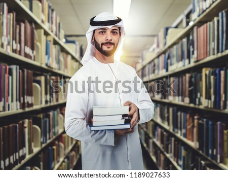 Arab student standing in library holding books on his arms. education concept. #1189027633