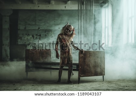 A full length portrait of a scary girl standing near a bed. Halloween. Horror film. Royalty-Free Stock Photo #1189043107