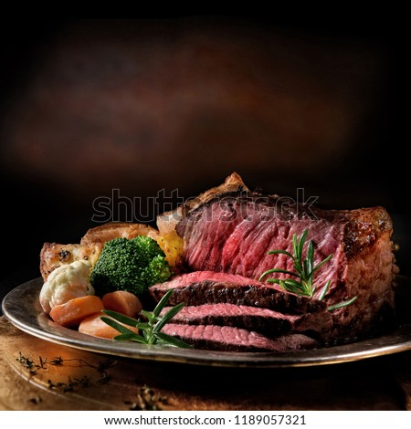 Rare roast beef meal with organic root vegetables and traditional Yorkshire pudding and roast potatoes. Shot against a dark rustic background with generous accommodation for copy space. #1189057321