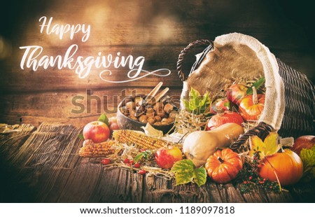 Hand written Thanksgiving invitation with a basket full of fresh harvest Like apple corn and pumpkins for Halloween #1189097818