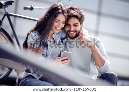 Young couple using smart phone while sitting on the stairs. #1189159831