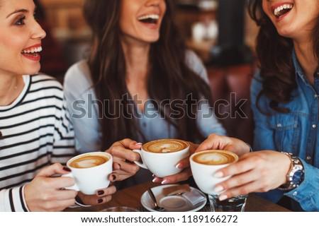 Three young women enjoy coffee at a coffee shop #1189166272
