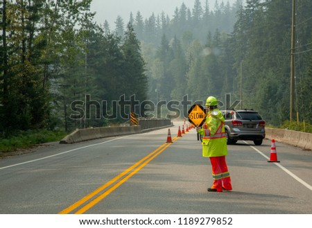 Slow sign was held by construction crew in the road with mountain background in Canada