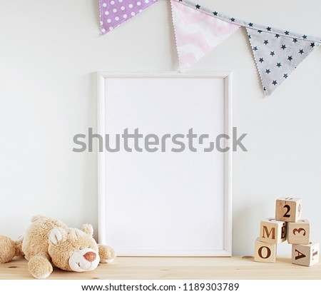White frame mock up for photo, print art, text or lettering, with kids room decorations and toys. Blank frame on wooden table.