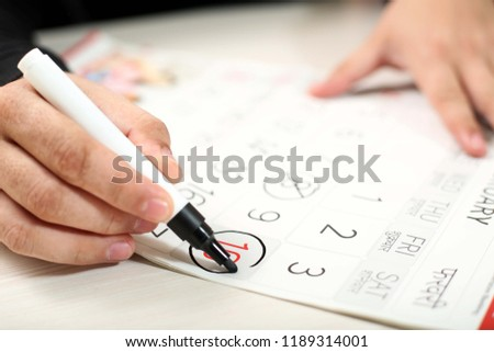 Man is marking holiday date on the calendar with marker.