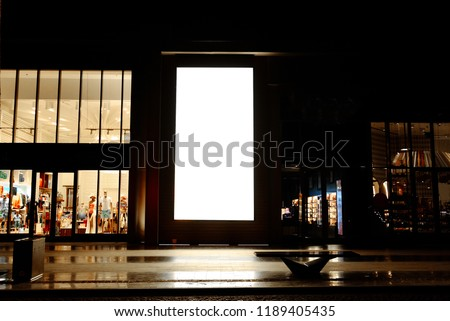Tall outdoor portrait blank digital signage light box  mock up near retail stores and restaurants taken at night, ideal for large posters, huge information boards, and marketing advertisement space. #1189405435