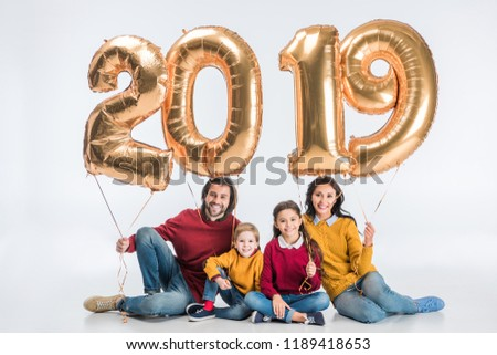 happy family holding sign 2019 made of golden balloons for new year isolated on white background