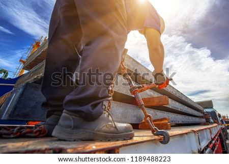 workers driver of the trailer lorry is lashing securing steel slab on the trailer, lashing securing goods by tightening chain for lashing before delivery  #1189488223