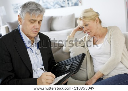 Doctor writing medical presciption to patient #118953049