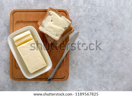 Butter or spread is in white butter-dish standing on a kitchen table and sandwich served on board ready to eat, view from above, space for a text #1189567825