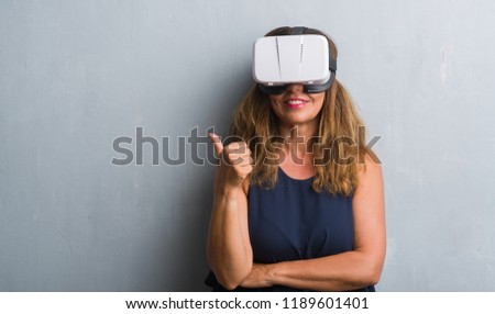 Middle age hispanic woman standing over grey grunge wall wearing virtual reality glasses happy with big smile doing ok sign  #1189601401