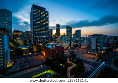Denver , Colorado Downtown City lights illuminate as the sun goes down behind the Rocky Mountains in the Mile High City night life and night lights turn on and glow