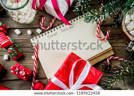 Christmas concept, preparation for xmas holidays, notepad for wish list, santa letter. to do list, with hot hot chocolate cup, Christmas tree decor, fir branches. Old wooden table copy space top view #1189622458