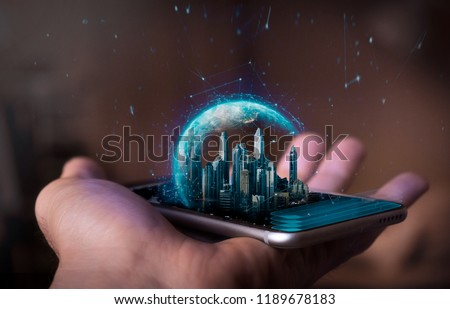 A man holds a futuristic phone in his hand, on which appears a futuristic metropolitan city with a holographic world. Concept of: business, connection, communication, people. #1189678183