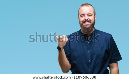Young caucasian hipster man over isolated background smiling with happy face looking and pointing to the side with thumb up. #1189686538