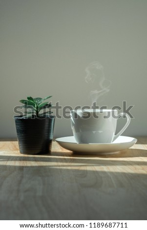 coffee cup on wooden table in the morning light. #1189687711