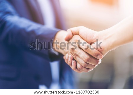 Concept of Negotiating business and handshake Gesturing People Connection Deal. close up hand of business man shaking hands with partner or customer on modern city background,fair play. film tone #1189702330