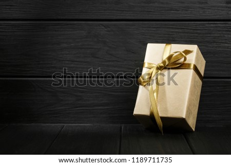 Gift box with golden ribbon on black wooden background top view. Discount gift for sale day. Flat lay with copy space. Holiday concept. #1189711735