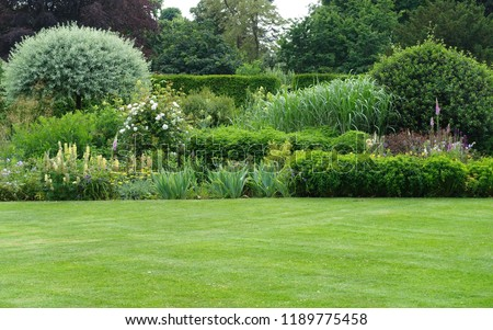 Scenic View of a Beautiful English Style Landscape Garden with a Green Mowed Lawn and Colourful Flower Bed #1189775458