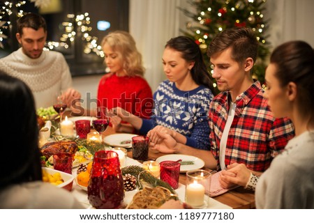 holidays and celebration concept - friends holding hands and praying while having christmas dinner at home #1189777180