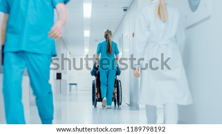 Shot of the Female Nurse Moving Patient in the Wheelchair Through the Hospital Corridor. Doing Procedures. Bright Modern Hospital with Friendly Staff. #1189798192