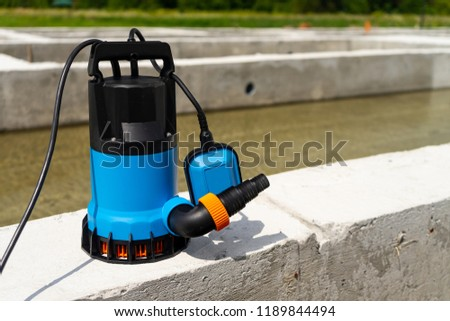 Submersible pump dewater construction site, pumping flood water sing deep well. #1189844494