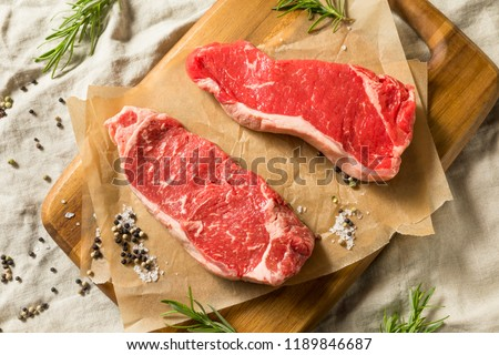 Raw Grass Fed NY Strip Steaks with Salt and Pepper Royalty-Free Stock Photo #1189846687