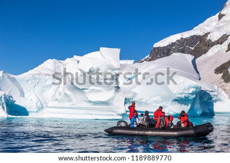 Boat full of tourists explore huge icebergs drifting in the bay near Cuverville island, Antarctic peninsula #1189889770