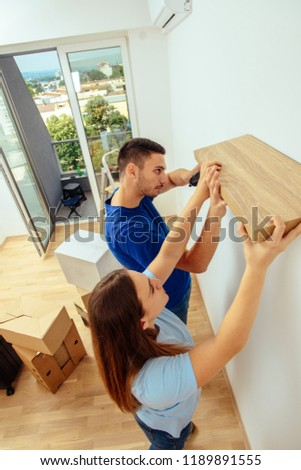 Couple installing bookshelf in their new apartment on the wall. young family decorating and moving in #1189891555