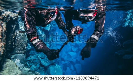 Snorkeling couple young man and woman taking pictures and filming underwater with action camera pointing out to the bottom, blue background crystal clear blue glacial water people wearing dry suits