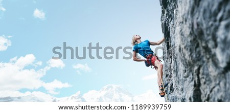 man rock climber with long hair. side view of young man rock climber in bright red shorts climbing the challenging route on the cliff on the blue sky background. rock climber climbs on a rocky wall. Royalty-Free Stock Photo #1189939759