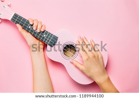 Woman hand with fashion manicure holding little pink ukulele on pink background. Fine female musician picture. Top view, flat lay.