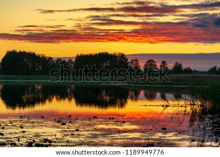 View on a lake during the spectacular sunset - mirror reflection of the sky and clouds in the water of lake #1189949776