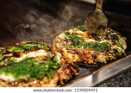 chef use spatula to cut the done okonomiyaki in half on the iron plate, and ready to give the delicious japanese traditional food to the customers #1190009491