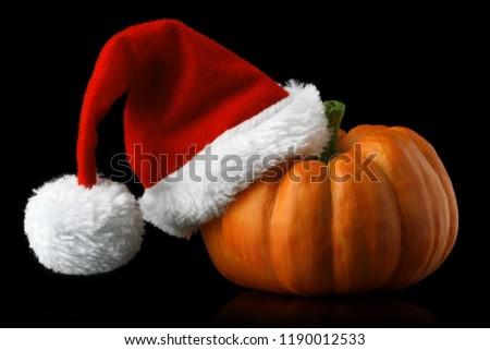 Single orange pumpkin with Christmas Santa hat isolated on black