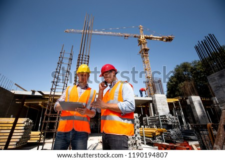 Structural engineer and architect dressed in orange work vests and  hard bats  discuss the construction process by the phone and use tablet  on the open building site near the crane #1190194807