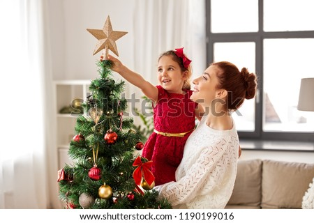 family, winter holidays and people concept - happy mother and little daughter decorating christmas tree at home #1190199016