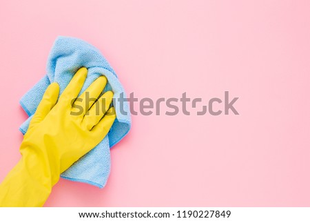 Employee hand in yellow rubber protective glove wiping pastel pink wall from dust with blue dry rag. General or regular cleanup. Commercial cleaning company. Copy space. Empty place for text or logo. #1190227849